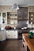 Modern country-house kitchen with wooden and stainless steel fronts; rustic, wooden kitchen island in foreground
