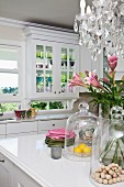 Elegant country-house kitchen with view of landscape through windows; summer bouquet in foreground below crystal chandelier