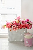 Bouquet of roses in white china vase next to pink ceramic pot with lid on windowsill