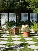 Delicate, rusty metal garden chairs and table on chequered pattern of stone slabs and squares of lawn