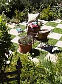Gartenfläche im Schachbrettmuster mit filigranen Vintage-Gartenmöbeln und einem großen, blühenden Terrakottatopf