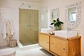 Retro, wooden sideboard with twin washbasins below mirrors on wall next to modern, glass shower cubicle