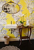 Modern sink and wooden console table with curved legs against yellow wallpaper with large urn motif
