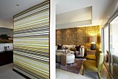 Partition wall with coloured stripes screening lounge with fifties armchairs and modern couch in open-plan interior
