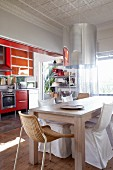 Dining area with modern wooden table and various chairs in front of kitchen with red units
