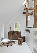 Tasteful leather armchair under sloping ceiling with animal-skin rug on white floor