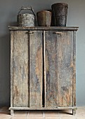 Old vessels on top of rustic cupboard against grey wall