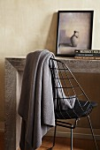 Table made from massive wooden slabs and grey woollen blanket hanging over delicate metal chair