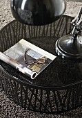 Open book and reading glasses on round table with glass top on grey rug