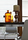 Large, antique candlestick next to brown vintage bottle on modern table in front of window