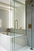 Indirect lighting in bathroom with grey wall tiles and sliding glass partition