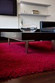 Coffee table with metal legs on red woollen rug