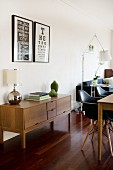 Open-plan interior with retro sideboard and black Eames chairs at dining table
