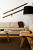 Scandinavian-style living room with beige couch, wooden chairs and antique skis on wall