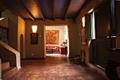 Große, dunkle Diele mit Terrakottfliesen, Holzbalkendecke und mit Blick ins Wohnzimmer
