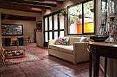 Weitläufiger Wohnraum mit dunklen Holzbalken an der Decke und Terrakottafliesen; im Vordergrund eine weisse Couch und ein antiker Wandtisch