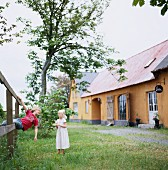 A boy and a girl playing in a garden, Sweden.