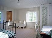 Geräumiges, helles Schlafzimmer mit einfachem Holzdielenboden und weisser Sitzbank