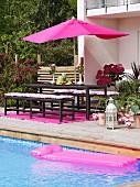 Holzterrasse mit pinkfarbenen Elementen neben azurblauem Swimmingpool