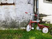 Verwitterte Hausecke mit daran lehnendem Dreirad