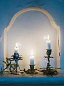 Brennende Kerzen in kunstvollen Kerzenhaltern