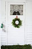 Weihnachtlich dekorierte Tür mit Spitzenvorhang am Glaseinsatz