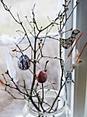Feather and decorations hanging on bare branches