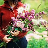 A woman holding a bouquet of purple flowers.