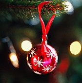 Rote Weihnachtskugel am Weihnachtsbaum hängend