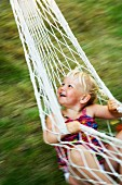 A happy girl swinging in a hammock.