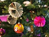 Weihnachtsschmuck aus Papier am Weihnachtsbaum hängend