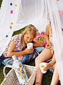 Two girls are having a picknick under a mosquito net.