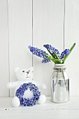 Teddy bear with wreath and posy of grape hyacinths