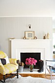 Antique upholstered armchair & modern leather chair in front of open fireplace with white mantel