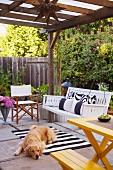 Dog lying on roofed terrace with porch swing