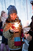 Girl wearing winter clothing looking at sparkler