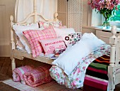 Nostalgic girl's bed with scatter cushions & blankets