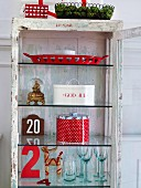 Open, glass-fronted cabinet with glasses & Christmas decorations