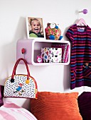Child's bedroom (detail) with shelf, scatter cushions, bag and child's clothes