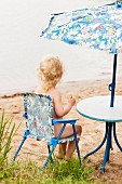 Toddler sitting on camping chair under parasol on beach (Södermanland, Sweden)