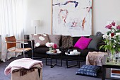 Modern living room with sofa, side tables, leather chair & painting
