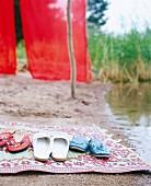 Slippers on rug on beach