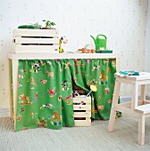 Child's potting table with storage space behind colourful curtains