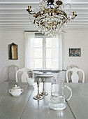 White interior with low ceiling, chandelier & dining table