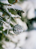 Silberne Weihnachtskugel an schneebedecktem Tannenzweig hängend