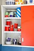 Crockery & groceries in open red kitchen cupboard