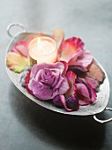 Tealight, petals and purple rose in silver dish