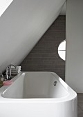 White bathtub under white sloping ceiling