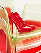 Red high-heeled shoes on stacked plastic chairs