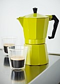 Yellow espresso maker and glasses of hot espresso